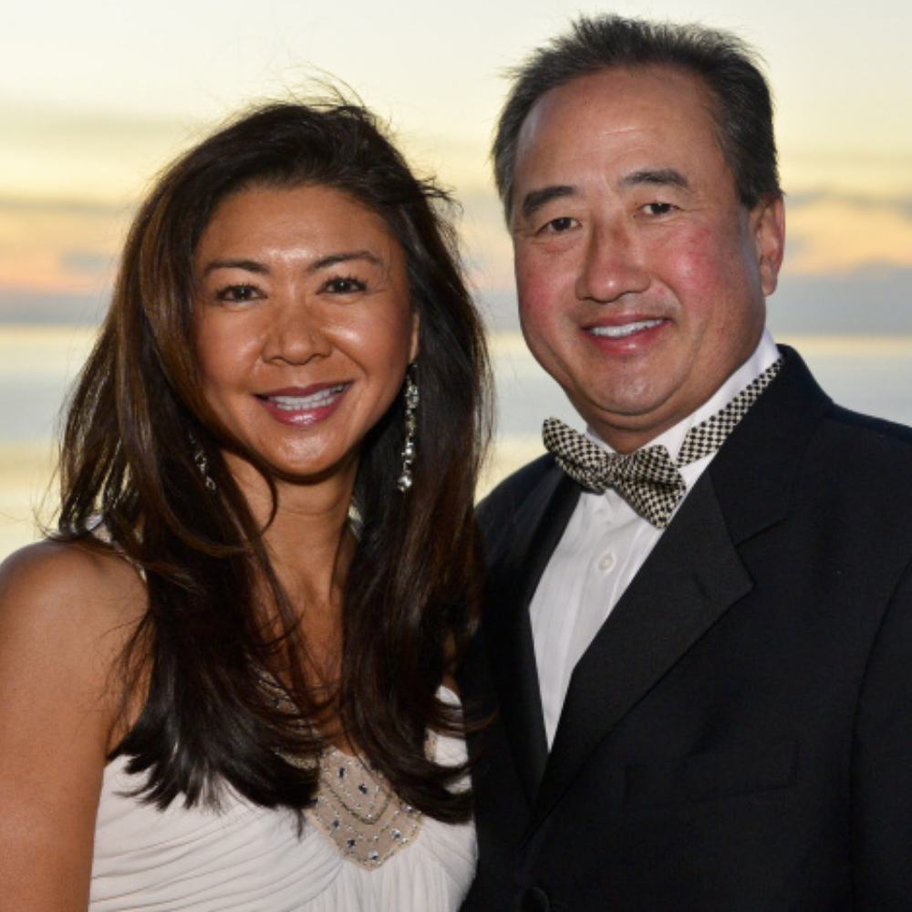 Portrait of Alumna Maggie Chang standing next to a man