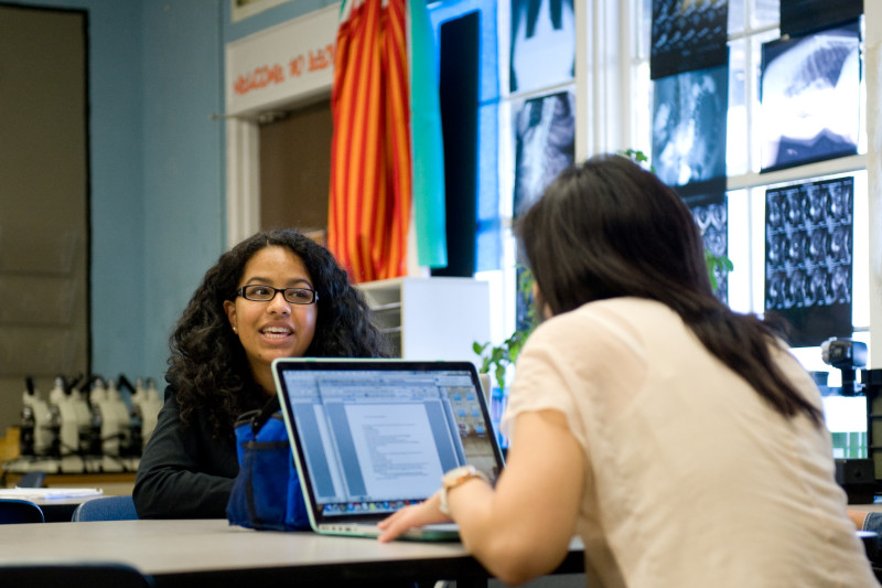 Photo of Crystal Calino and Stephanie Hsu in a classroom conversing with each other
