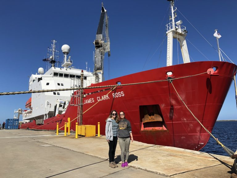 Researchers near a red ship by the ocean