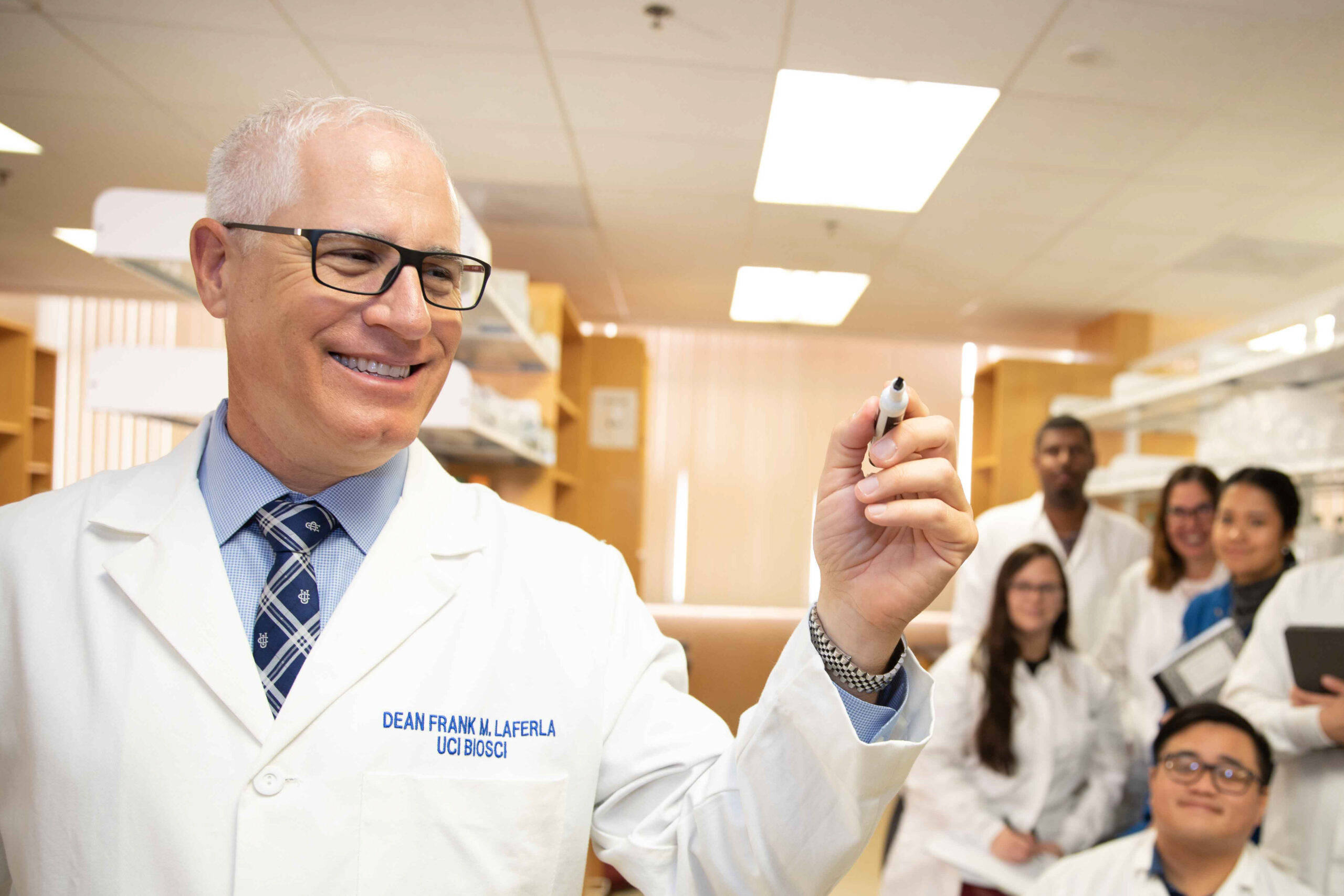 Dean Frank LaFerla in lab coat with lab staff