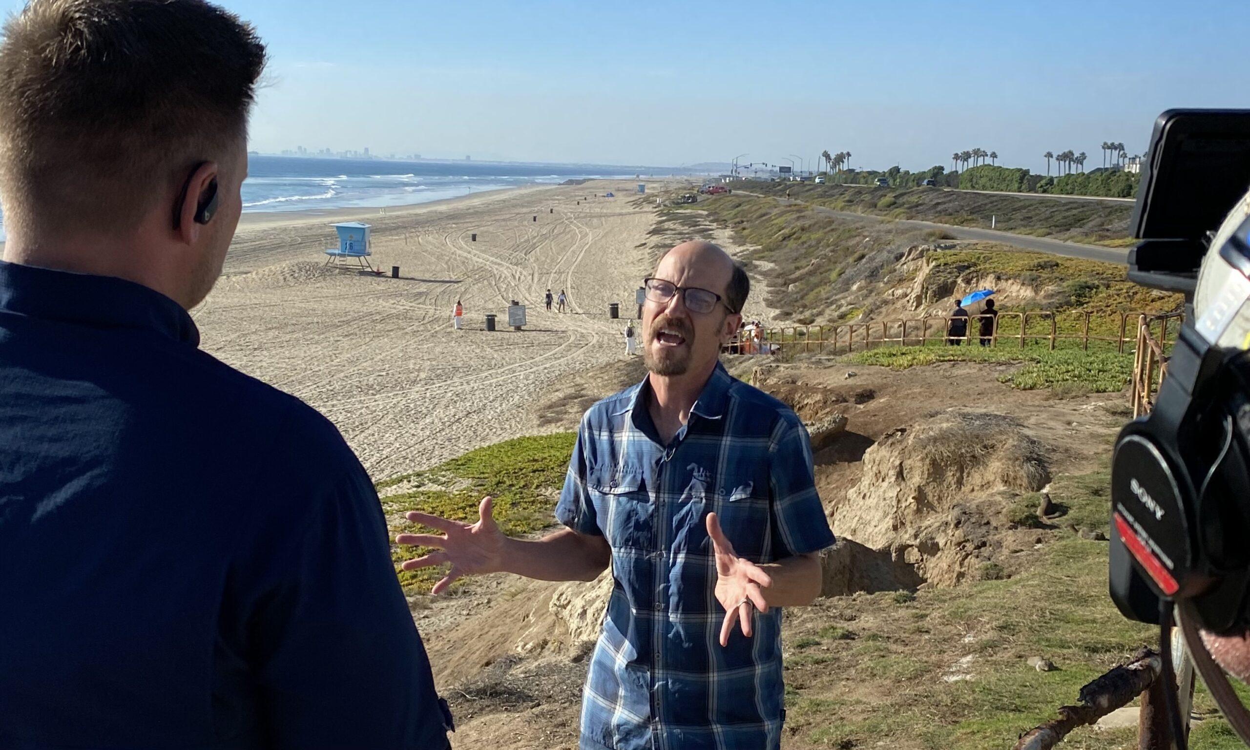 Reporter interviewing Dr. Matt Bracken at the beach